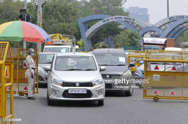Police personnel screen commuters for identity cards at Uttar Pradesh-Delhi border after it was sealed, on May 13, 2020 in Noida, India.
