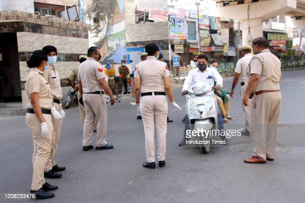 Police personnel screen for identity cards during the first day of national lockdown imposed by PM Narendra Modi to curb the spread of coronavirus,...