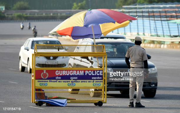 Police personnel screens vehicles crossing barricades placed along the Gurugram-Delhi Sirhaul border at National Highway-48 near Ambience Mall during...