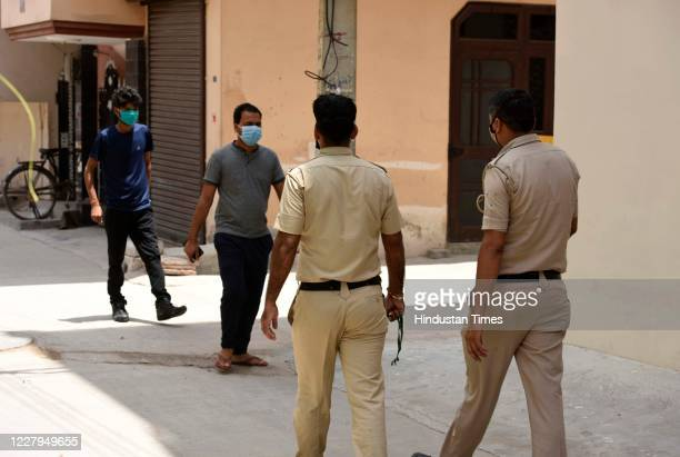 Police personnel seen while accompanying an Anganwadi worker during a door-to-door COVID-19 screening at Om Nagar Dharamshala, Sector-11 near Mata...
