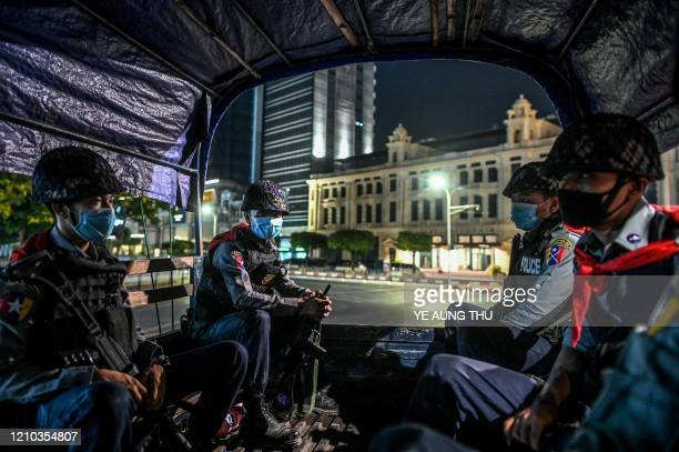 TOPSHOT Police personnel sit on a vehicle as they patrol on a road amid concerns over the spread of the COVID19 coronavirus in Yangon on April 18...