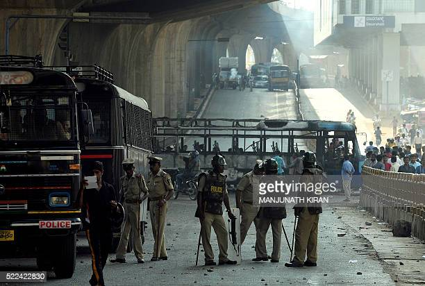 Police personnel stand gaurd near burnt buses after violence that followed a protest by garment factory workers in Bangalore on April 19 2016...