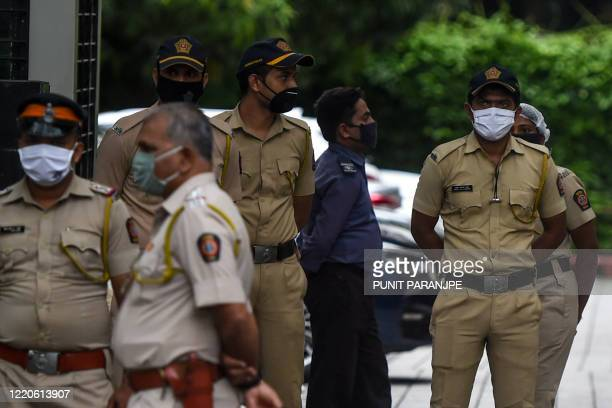 Police personnel stand guard as they set up barricades and extra deployment of personnel outside the Consulate General of China in Mumbai on June 17...