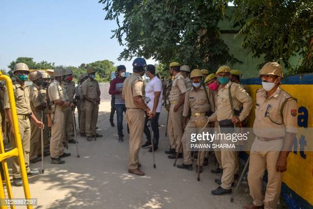 Police personnel stand guard blocking a road near the premises of the relatives of the 19-year-old woman allegedly gang-raped and killed by four men...