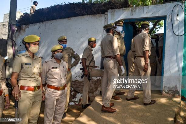 Police personnel stand guard near the premises of the relatives of the 19-year-old woman allegedly gang-raped and killed by four men in Bool Garhi of...
