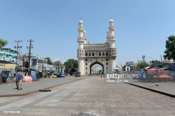 Police personnel stand guard on a deserted road in front of historical Charminar monument during a one-day nationwide Janata curfew imposed as a...