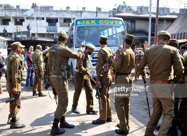 Police personnel stand near the damaged bus at the site of a grenade blast at Bus Stand on March 7 2019 in Jammu India A teenager was killed and 32...