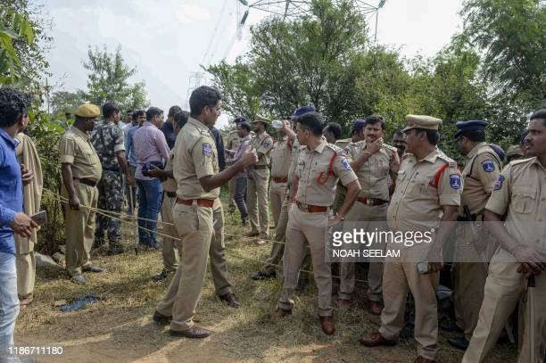 Police personnel stand near the site where they shot dead four detained gang-rape and murder suspects in Shadnagar, some 55 kilometres from...
