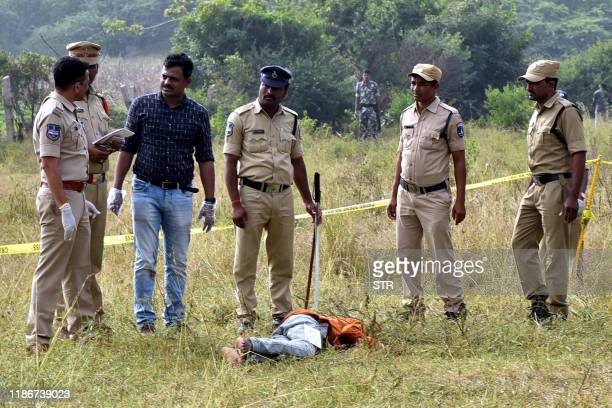 Police personnel stand next to the body of a man at the site where Police officers shot dead four detained gang-rape and murder suspects in...