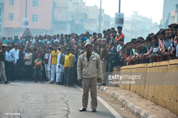 A Police personnel stands guard along a road as onlookers gather following a factory fire in Anaj Mandi area of New Delhi on December 8 2019 At least...