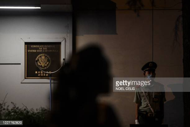 Police personnel stands guard as a pedestrian walks past at the entrance to the US consulate in Chengdu, southwestern China's Sichuan province, on...