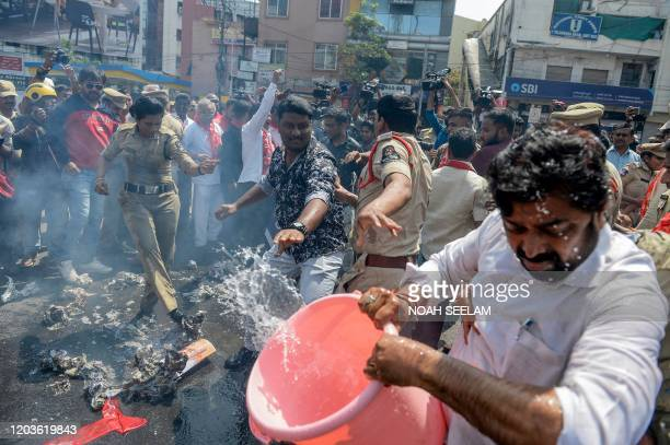 TOPSHOT A police personnel stops members of Communist Party of India to burn an effigy representing Union Home Minister Amit Shah to demend his...