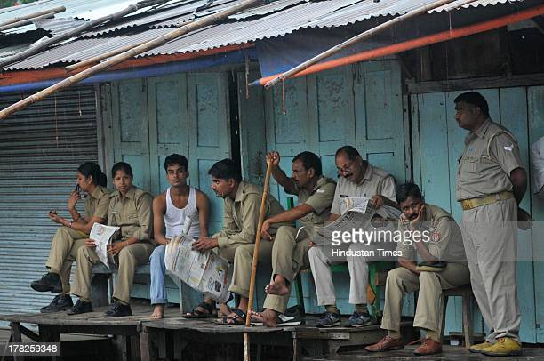 Police personnel takes rest as it rains on August 27 2013 in Ayodhya India Two days after the failed Parikarma attempt by Vishwa Hindu Parishad...