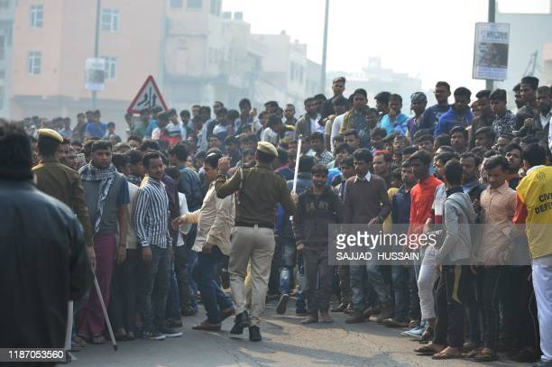 Police personnel try to clear a road as onlookers gather following a factory fire in Anaj Mandi area of New Delhi on December 8 2019 At least 43...