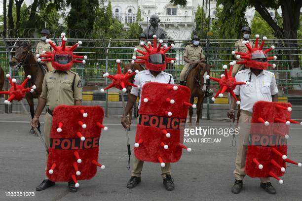 Police personnel wearing a Covid-19 coronavirus-themed helmets, shields and battons stand in formation as they take part in awareness campaign...