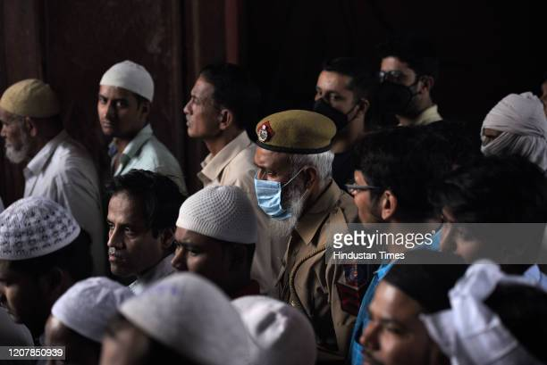 Police personnel wearing a protective face mask during Friday prayers amid Coronavirus outbreak in the country, at Jama Masjid on March 20, 2020 in...