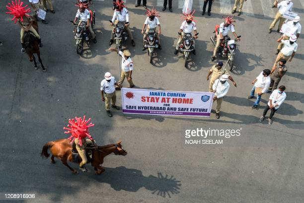 Police personnel wearing coronavirus-themed helmets ride on horses and bikes as they participate in a awareness campaign during a 21-day...