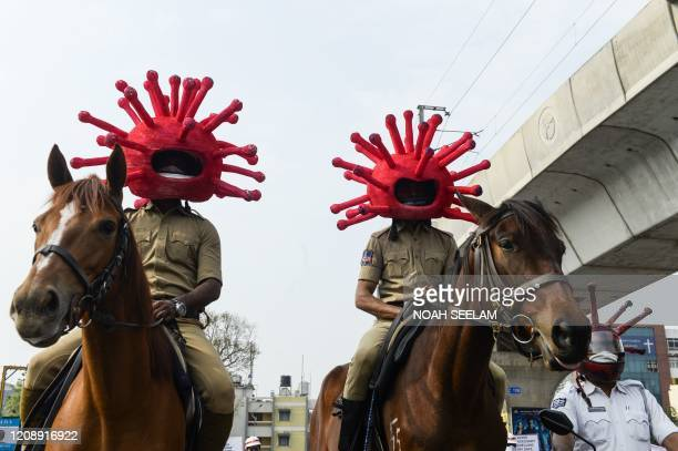 Police personnel wearing coronavirus-themed helmets ride on horses as they participate in a awareness campaign during a 21-day government-imposed...
