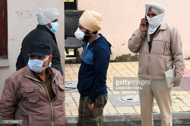 Police personnel wearing facemasks amid concerns over the spread of the COVID-19 novel coronavirus speak with Indiannational Jasbir Singh , who...