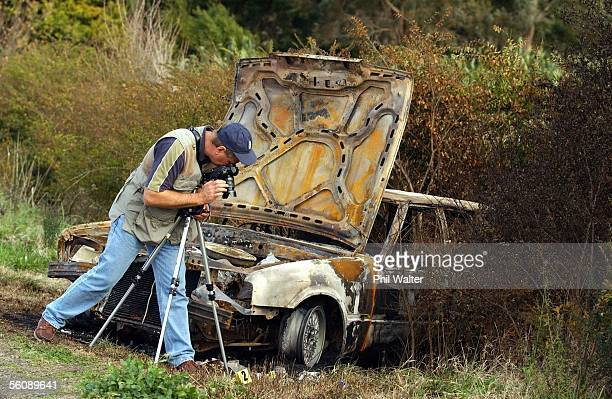A police photographer photographs the burnt out gang car near the small town of Taneatua after an overnight gang related shooting left three people...