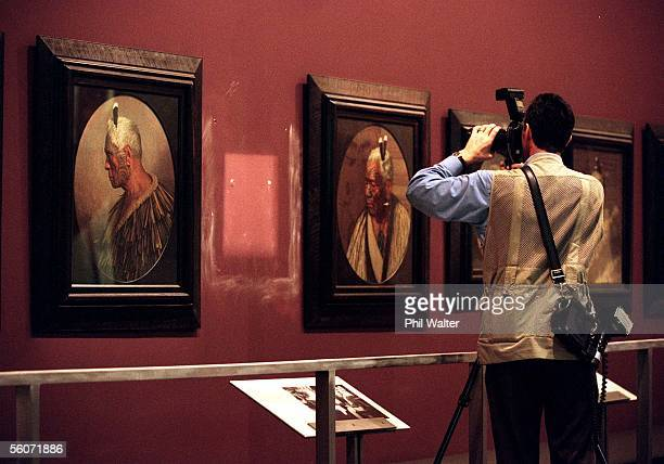 A police photographer photographs the empty space where the Charles F Goldie painting of Hera Puna Memories of a Heroine lay before it was stolen...