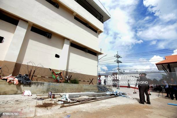 Police point at holes through which 20 ethnic Uighurs escaped from an immigration detention centre in Sadao district in the southern Thai province of...