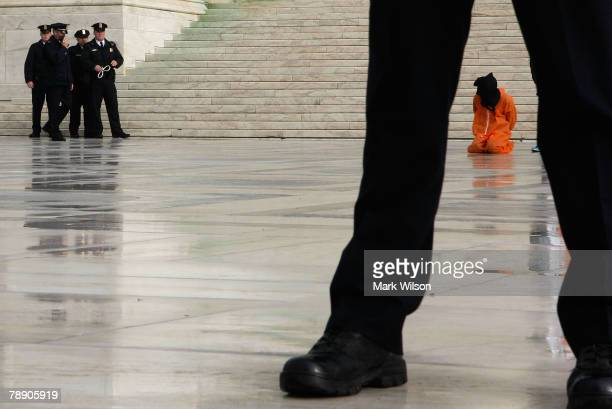 Police prepare to arrest an activist dressed in a orange jump suit in front of the US Supreme Court January 11 2007 in Washington DC Several...