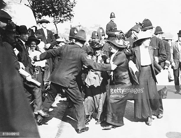 Police prevent suffragist Emmeline Pankhurst and her two daughters Chistabel and Sylvia from entering Buckingham Palace to present a petition to the...