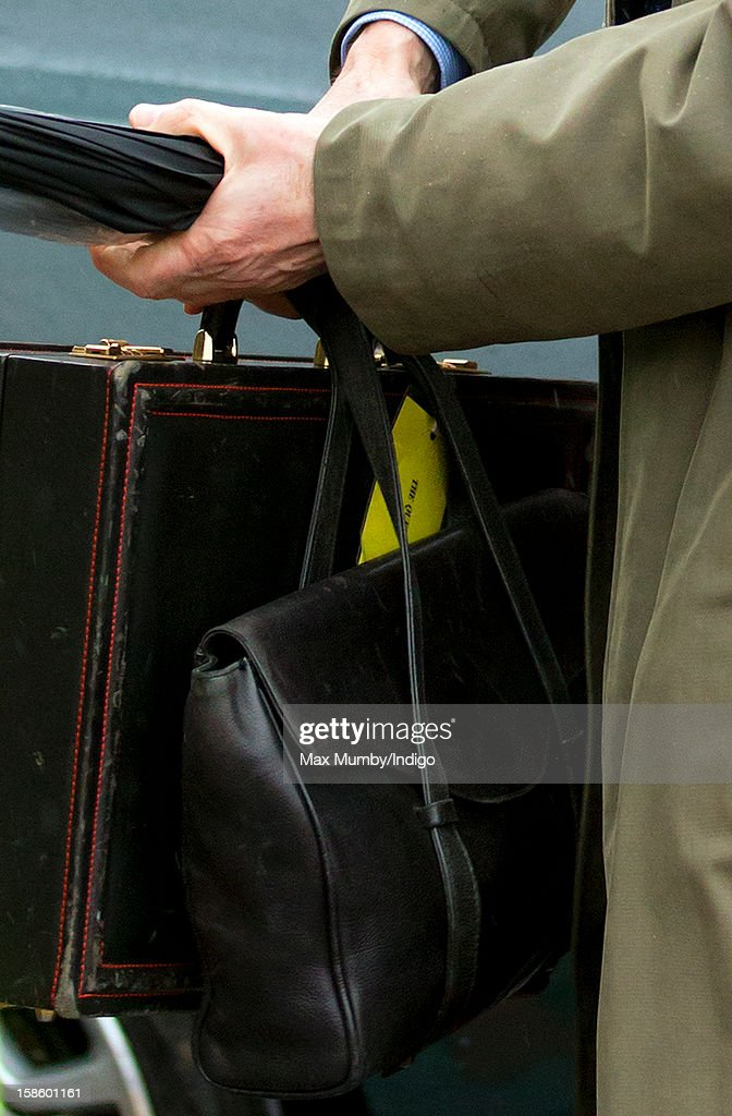 A Police Protection Officer carries a briefcase belonging to Queen Elizabeth II as she, accompanied by Prince Philip, Duke of Edinburgh, arrives at King's Cross Railway Station to take the train to King's Lynn on route to her Norfolk Estate, Sandringham House, for her traditional Christmas Break on December 20, 2012 in London, England.