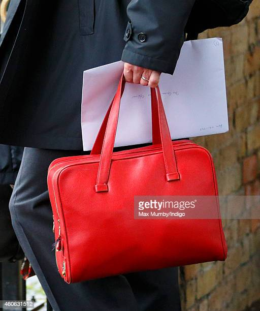 A Police Protection Officer seen carrying Queen Elizabeth II's red bag as she arrives at King's Lynn Railway Station after taking the train from...