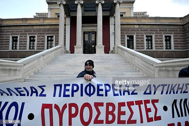 Police protester holds a banner in front of the old Greek Parliament during a protest against austerity measures in Athens on December 14 2010 More...