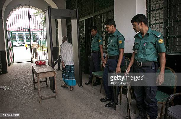 Police provide security with a metal detector that was installed after last year's attack at the Hussaini Dalan Shia shrine March 20 2016 in Dhaka...