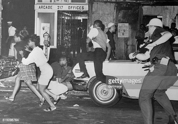Police pursue people during riots in Harlem sparked by the killing of a 15 year old boy by police Stores were looted and about 25 persons were...