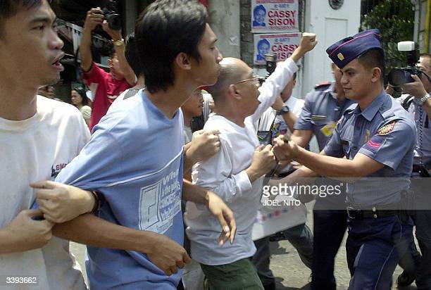 Police push away antigovernment demonstrators protesting deployment of Philippine troops in Iraq from the gate of the Malacanang presidential palace...