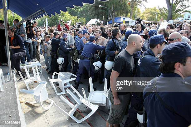 Police push back protesters from the officials' stand during the annual student's parade in the city of Iraklion Crete island on October 28...