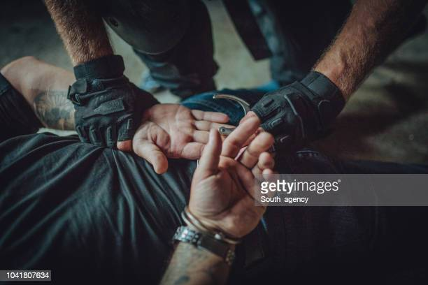 police putting handcuffs on a man - fugitive stock photos and pictures