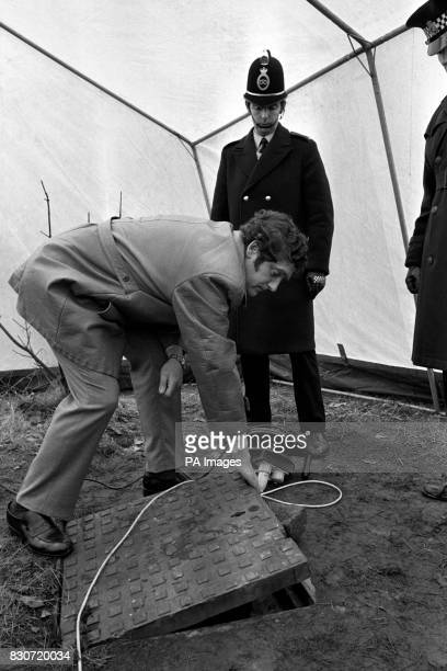 Police raise a manhole cover at Bathpool Park at Kidsgrove Staffordshire to examine the entrance to the shaft at the foot of which was found the body...