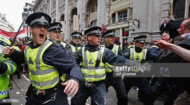 Police react to protesters as they block access to a branch of RBS stopping anti capitalist and climate change activists demonstrating in the City of...