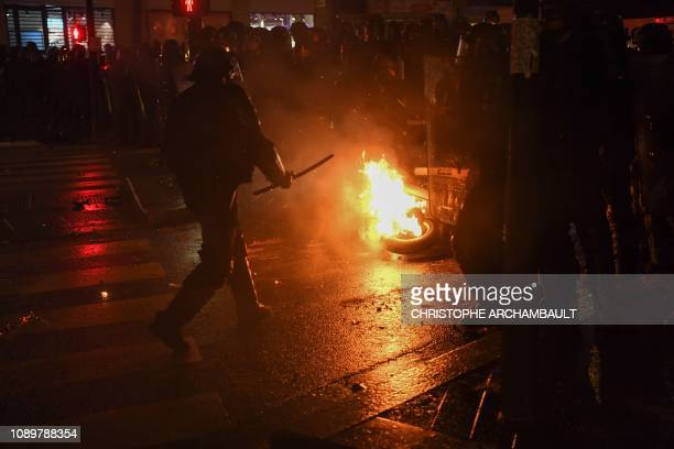 Police remove a burning scooter during clashes at an antigovernment demonstration called by the yellow vests movement on the Place de la Republique...