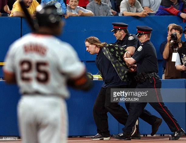 Police remove a field-running fan as San Francisco Giant slugger Barry Bonds waits to resume play in the top of the ninth inning against the Toronto...