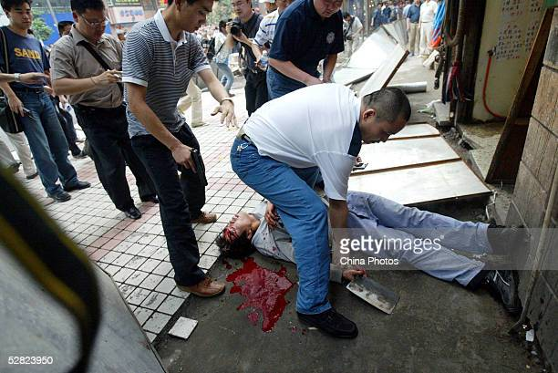 Police remove a kidnapper's body after he was shot by police on May 14 2005 in Chongqing Municipality China A Chinese man held a young girl hostage...