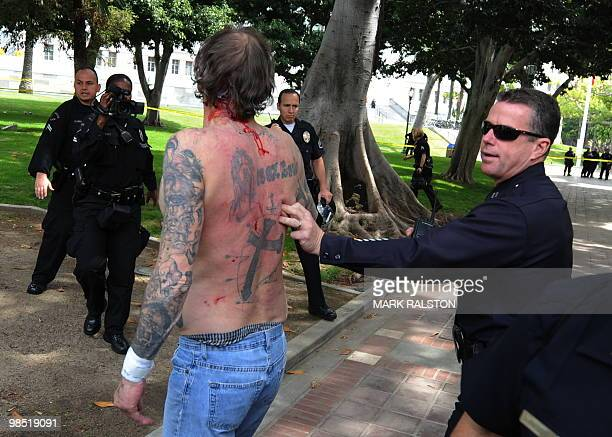 Police remove a man with nazi skin tattoo's after he was beaten by an angry crowd of counterprotesters before the neonazi group The American National...