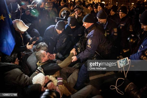 Police remove a protester on Budapest's famous Szechenyi Chain Bridge after police blocked them from leaving after attending a demonstration against...