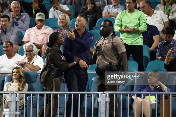 Police remove a spectator after he argued with Nick Kyrgios of Australia in his match against Dusan Lajovic of Serbia during day seven at the Miami...