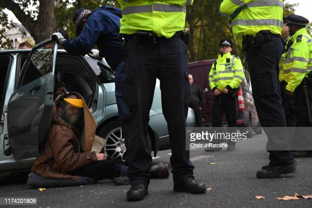 Police remove an Extinction Rebellion protester who has barricaded himself inside a car in Westminster on October 7 2019 in London England Climate...
