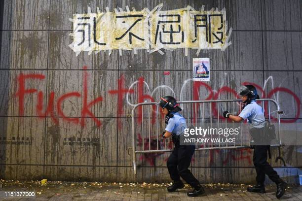 Police remove barricades under a poster displayed on a wall with remnants of thrown eggs and graffiti sprayed by protesters outside the police...