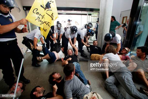 Police remove protesters from the offices of the French Payment and Services Agency in Limoges central France on August 29 during a demonstration by...