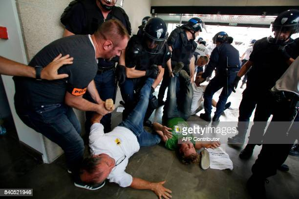 TOPSHOT Police remove protesters from the offices of the French Payment and Services Agency in Limoges central France on August 29 during a...