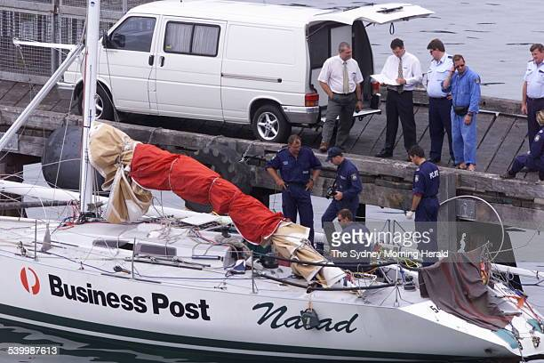 Police remove the body of crewman and the captain of Business Post Naiad who died during the Sydney to Hobart yacht race after the vessel was towed...
