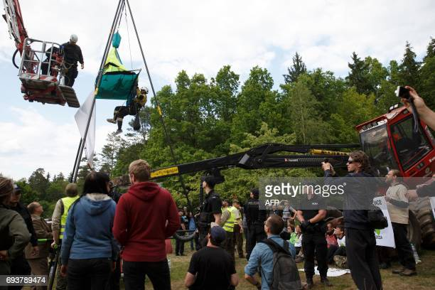 Police removes an environmental activist blocking logging machines to stop cutting the trees of the Bialowieza forest in Czerlonka Poland on June 8...